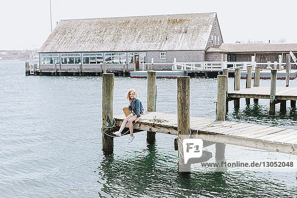Junge Frau auf Holzpier sitzend  Porträt  Menemsha  Martha's Vineyard  Massachusetts  USA