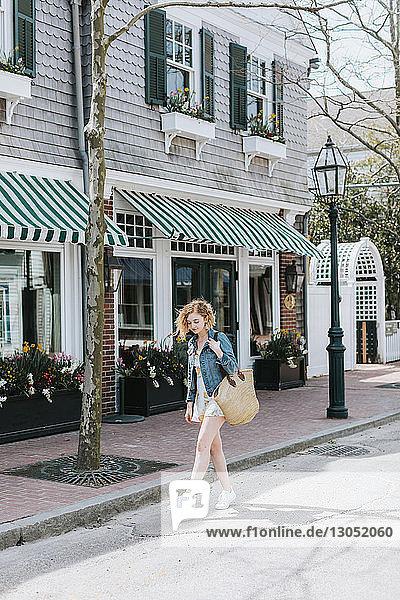 Junge Frau schlendert mit einer Strohtasche über die Straße  Menemsha  Martha's Vineyard  Massachusetts  USA