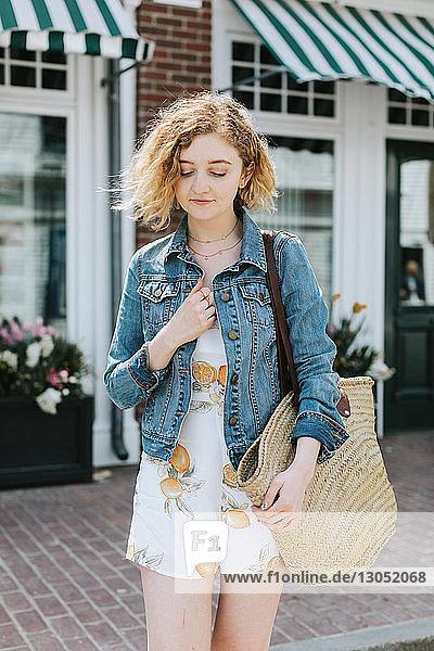 Junge Frau auf der Strasse  die eine Strohtasche trägt  Menemsha  Martha's Vineyard  Massachusetts  USA