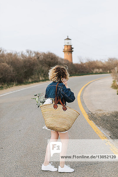 Young woman on rural road looking at lighthouse  rear view  Menemsha  Martha's Vineyard  Massachusetts  USA