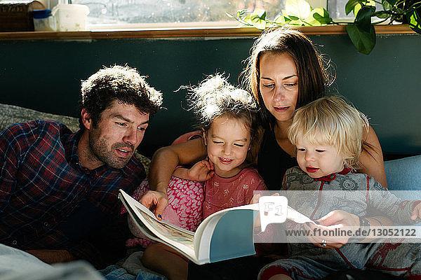 Eltern  die Kindern im Bett vorlesen