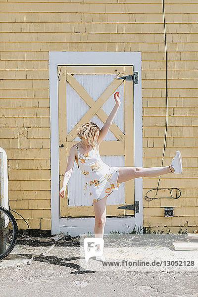 Young woman in front of building kicking her leg up  Menemsha  Martha's Vineyard  Massachusetts  USA