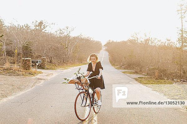 Young woman riding bicycle on rural road  Menemsha  Martha's Vineyard  Massachusetts  USA
