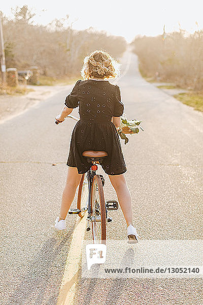 Young woman riding bicycle on rural road  rear view  Menemsha  Martha's Vineyard  Massachusetts  USA