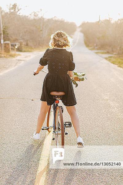 Junge Frau fährt Fahrrad auf einer Landstraße  Rückansicht  Menemsha  Martha's Vineyard  Massachusetts  USA