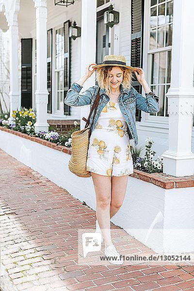 Junge Frau  die mit einem Strohboot auf dem Bürgersteig spazieren geht  Menemsha  Martha's Vineyard  Massachusetts  USA