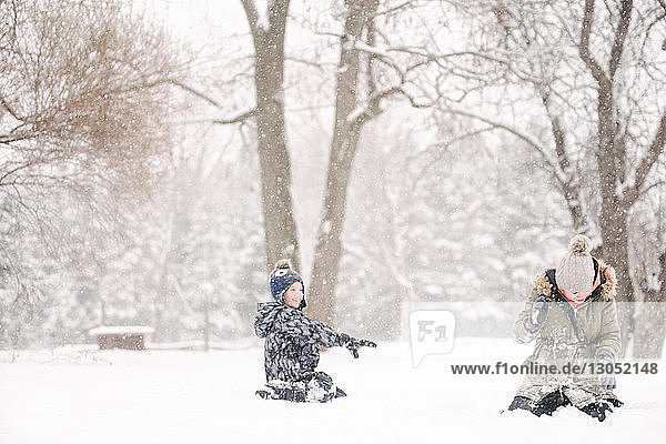 Junge wirft Schneeball auf Schwester