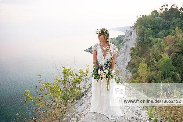 Braut mit Brautstrauss auf einer Klippe an der Küste  Scarborough Bluffs  Toronto  Kanada