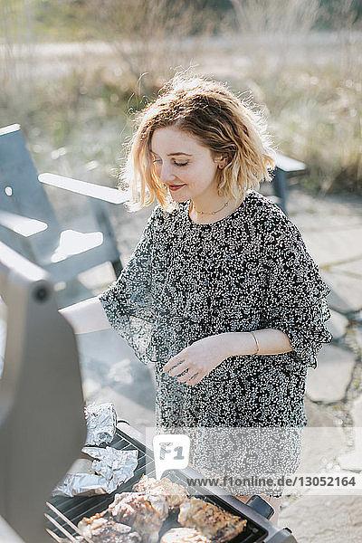 Young woman cooking on barbecue  Menemsha  Martha's Vineyard  Massachusetts  USA