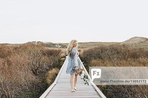 Junge Frau trägt einen Blumenstrauss auf der Dünenpromenade an der Küste  Menemsha  Martha's Vineyard  Massachusetts  USA