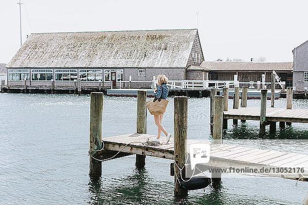 Junge Frau beim Spaziergang am Holzpier  Menemsha  Martha's Vineyard  Massachusetts  USA