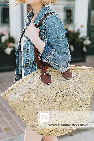 Young woman strolling along street carrying straw bag  mid section  Menemsha  Martha's Vineyard  Massachusetts  USA