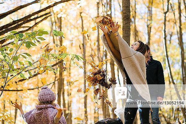 Mutter und Tochter werfen Herbstblätter im Wald in die Luft