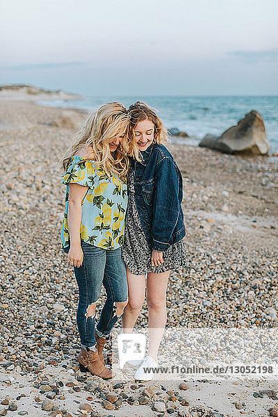 Zwei junge Frauen umarmen sich am Strand,  Menemsha,  Martha's Vineyard,  Massachusetts,  USA