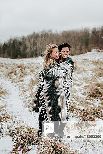 Couple wrapped in blanket in snowy landscape  Georgetown  Canada