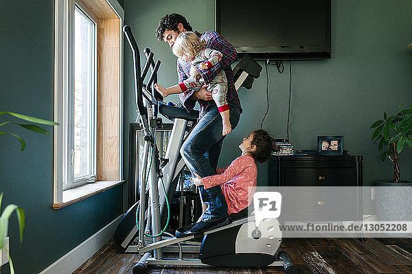 Vater und Kinder spielen auf einer elliptischen Maschine