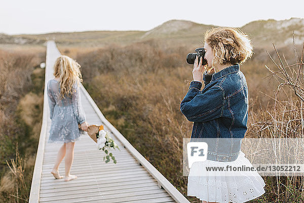Young woman photographing friend on coastal dune boardwalk  Menemsha  Martha's Vineyard  Massachusetts  USA