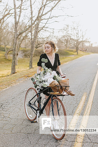 Young woman standing by bicycle with bunch of flowers on rural road  Menemsha  Martha's Vineyard  Massachusetts  USA