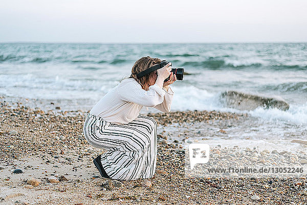 Young woman taking photographs from beach  Menemsha  Martha's Vineyard  Massachusetts  USA
