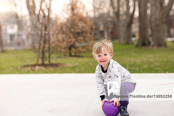 Junge spielt Ball im Park