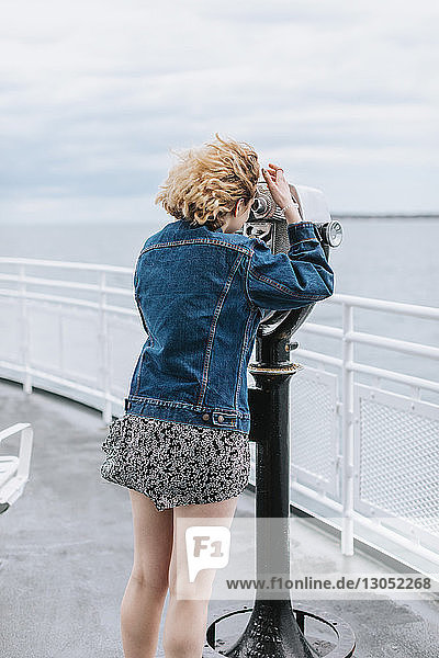 Young woman looking out to sea through coin operated binoculars  Menemsha  Martha's Vineyard  Massachusetts  USA