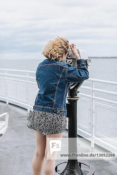 Junge Frau  die durch ein münzbetriebenes Fernglas auf das Meer schaut  Menemsha  Martha's Vineyard  Massachusetts  USA