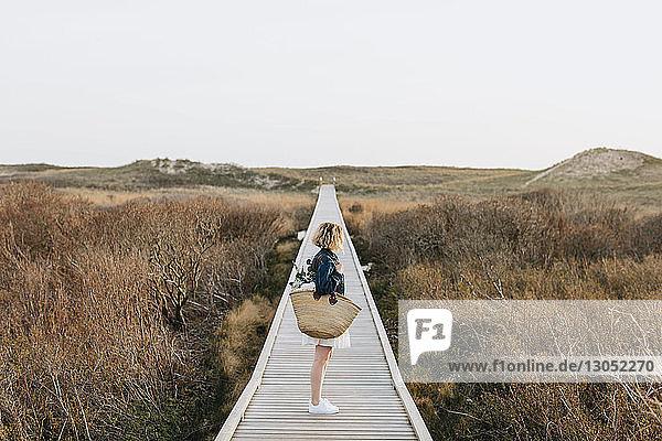 Lone young woman looking out from coastal dune boardwalk  Menemsha  Martha's Vineyard  Massachusetts  USA