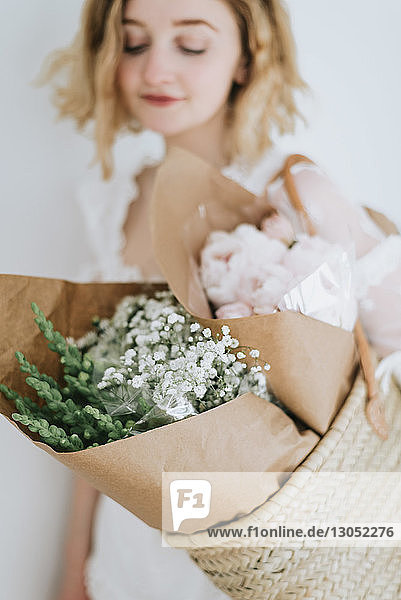 Young woman carrying straw basket with bunches of flowers