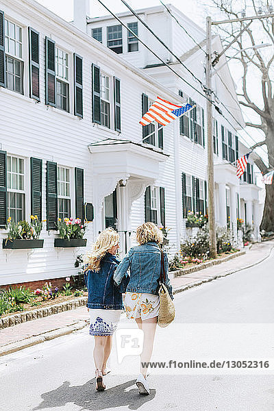 Two young female friends strolling along village road  rear view  Menemsha  Martha's Vineyard  Massachusetts  USA
