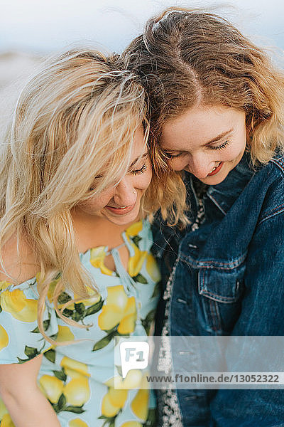 Two young women hugging on beach  close up  Menemsha  Martha's Vineyard  Massachusetts  USA