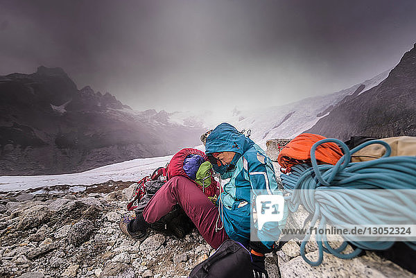 Rock climber by climbing equipment shielding from extreme weather  El Chaltén  south Patagonia  Argentina