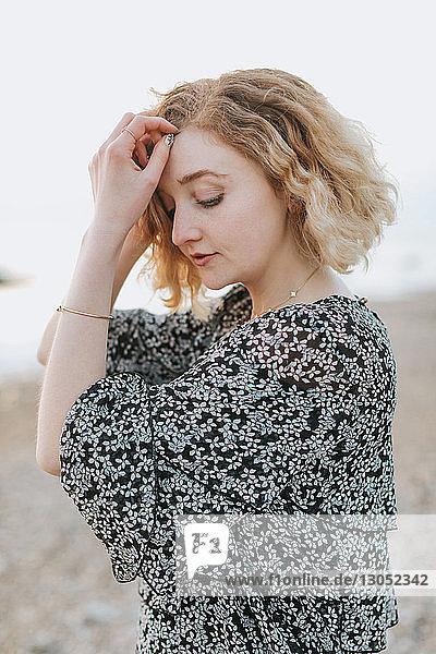 Young woman on beach with hands in hair  Menemsha  Martha's Vineyard  Massachusetts  USA
