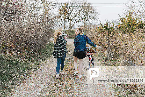 Two young women pushing bicycle on rural dirt track  rear view portrait  Menemsha  Martha's Vineyard  Massachusetts  USA