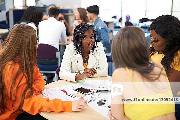 Weibliche Hochschulstudentinnen diskutieren Projekt im Klassenzimmer