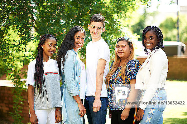 Teenage boy and higher education students on college campus  portrait