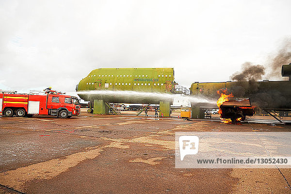 Firemen training  spraying water from fire engine at mock airplane