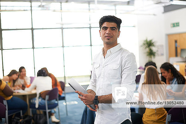 Young male higher education student in college classroom,  portrait