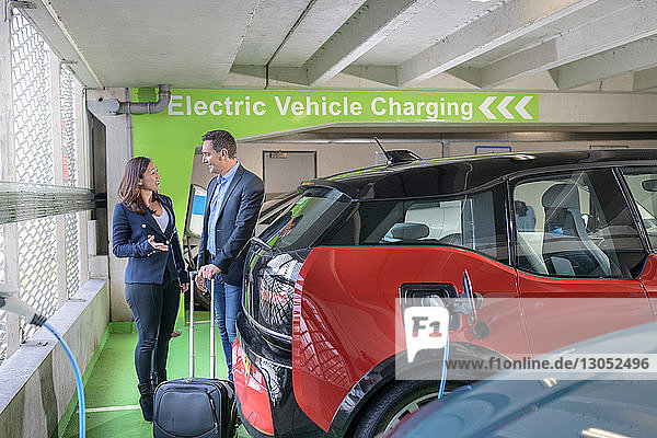 Man and woman charging electric car at charge bay  Manchester  UK
