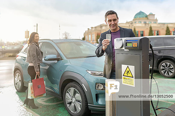 Man and woman charging electric car at car charging park  Manchester  UK