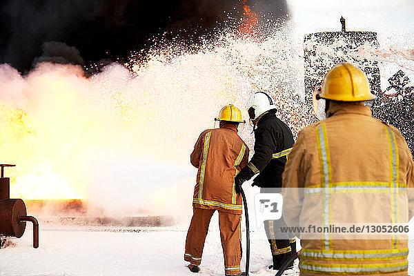 Firemen training  team of firemen spraying firefighting foam on fire at training facility  rear view