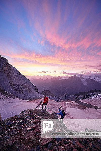 Hikers climbing rock at sunset  Mont Cervin  Matterhorn  Valais  Switzerland