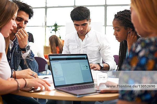 Weibliche und männliche Hochschulstudenten arbeiten im Team und benutzen den Laptop im Klassenzimmer der Hochschule