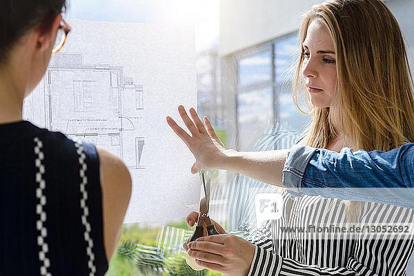 Kollegen diskutieren über Pläne an Glaswand