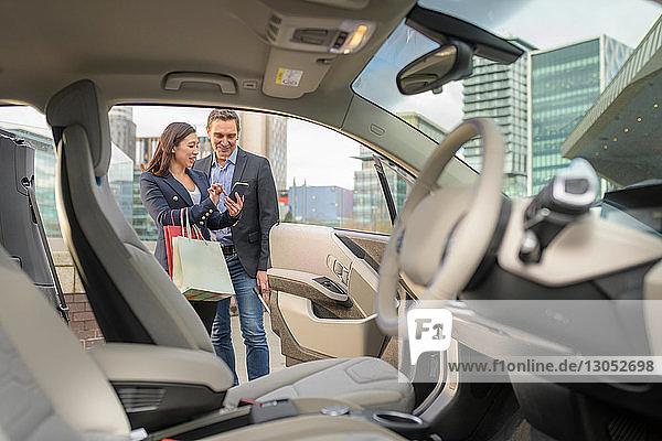 Mann und Frau überprüfen Autokosten über Mobiltelefon-App  Manchester  UK