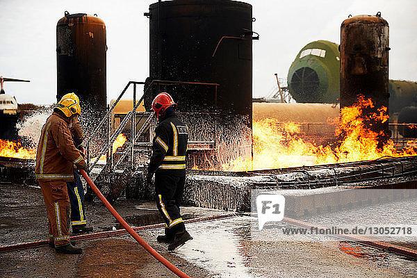 Firemen training  spraying firefighting foam onto oil storage tank fire at training facility