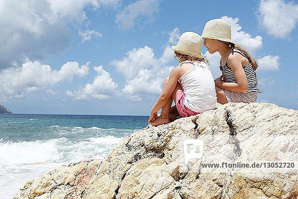 Zwei Mädchen schauen vom Felsen aufs Meer hinaus  Scopello  Sizilien  Italien