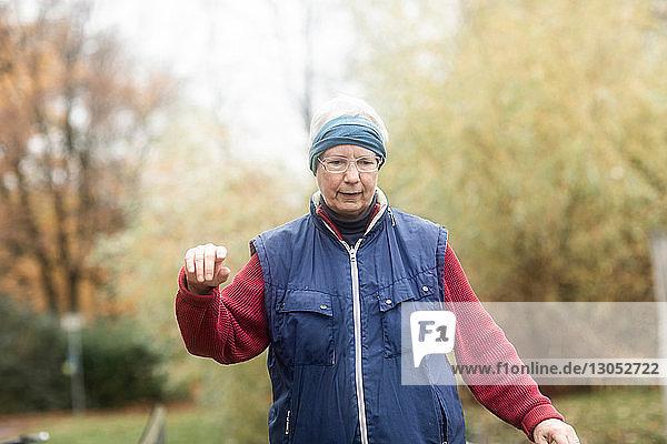 Ältere Frau geht im Park spazieren