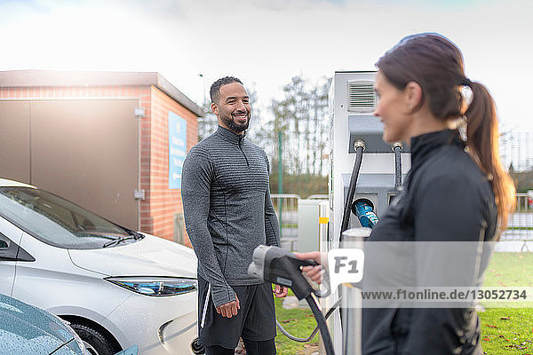 Sportsman and woman charging electric car at charging bay  Manchester  UK