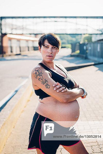 Schwangere Frau in Trainingskleidung bei Sonnenschein