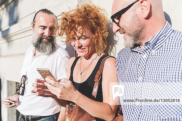 Mittelgroße erwachsene Frau und männliche Freunde lehnen an der Wand und schauen auf ein Smartphone